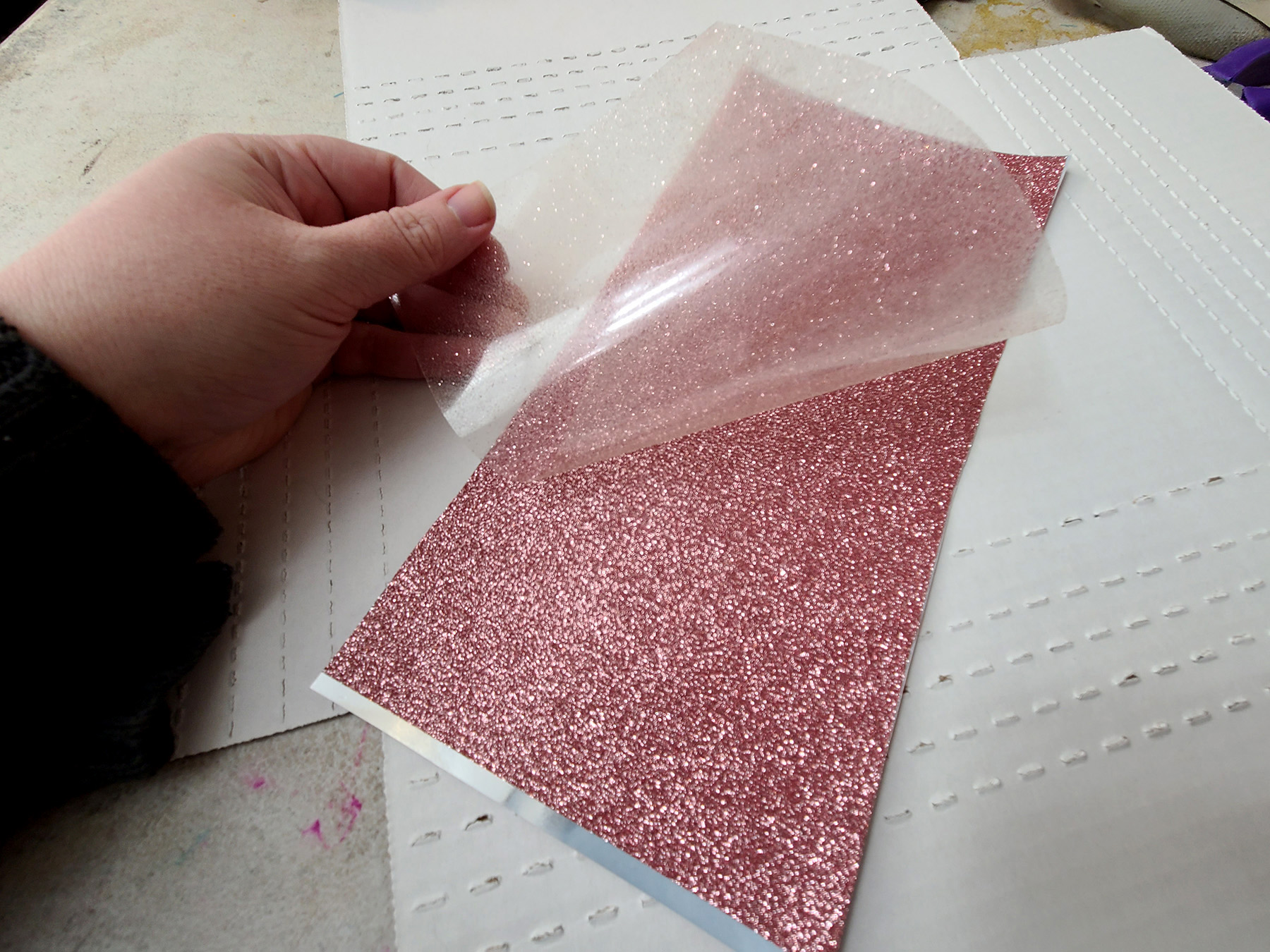 A hand peels a clear plastic layer off the surface of a piece of pink glitter vinyl.