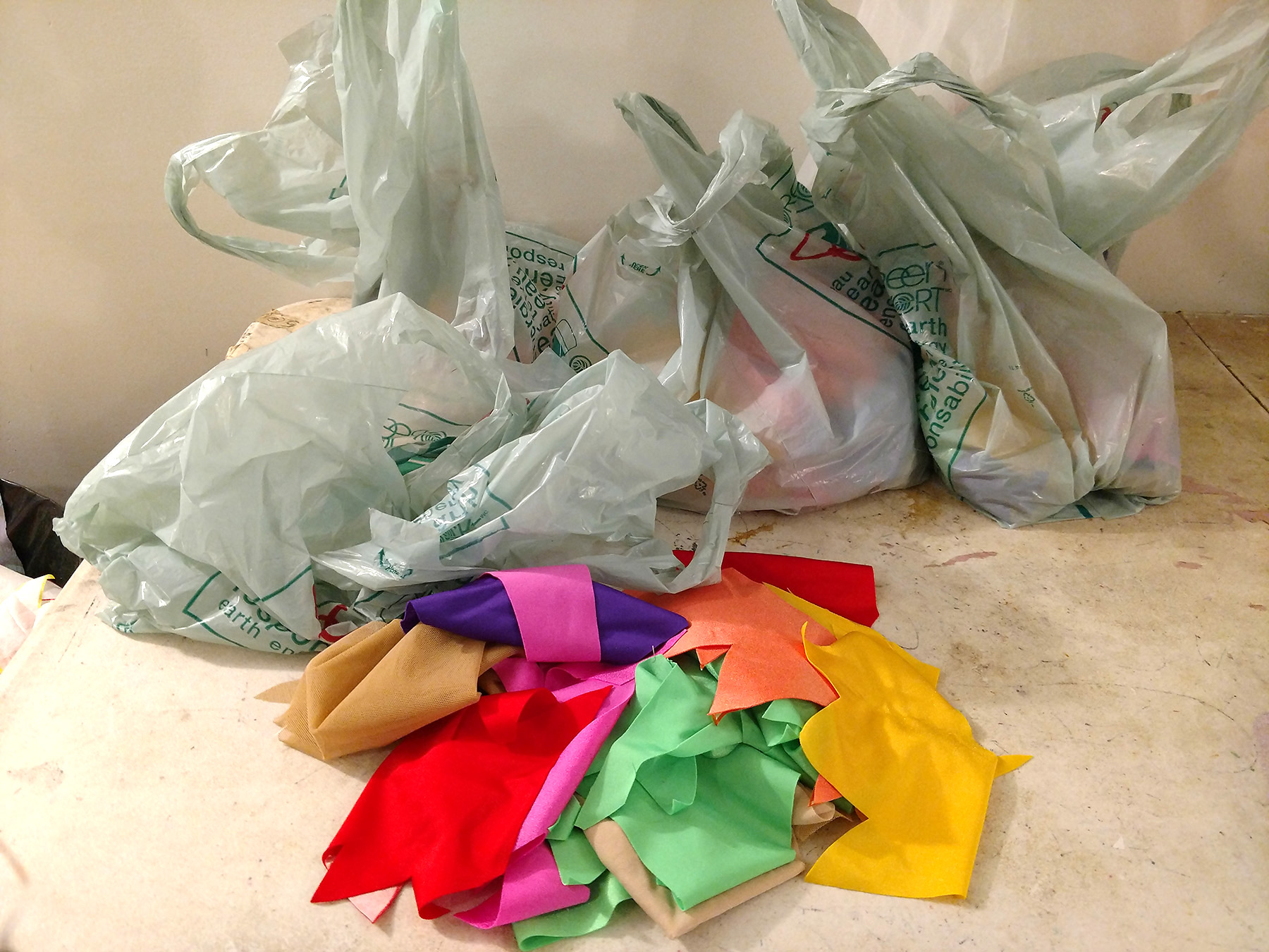 Several grey coloured grocery bags of fabric pieces, lined up behind a pile of colourful spanedx fabric pieces.