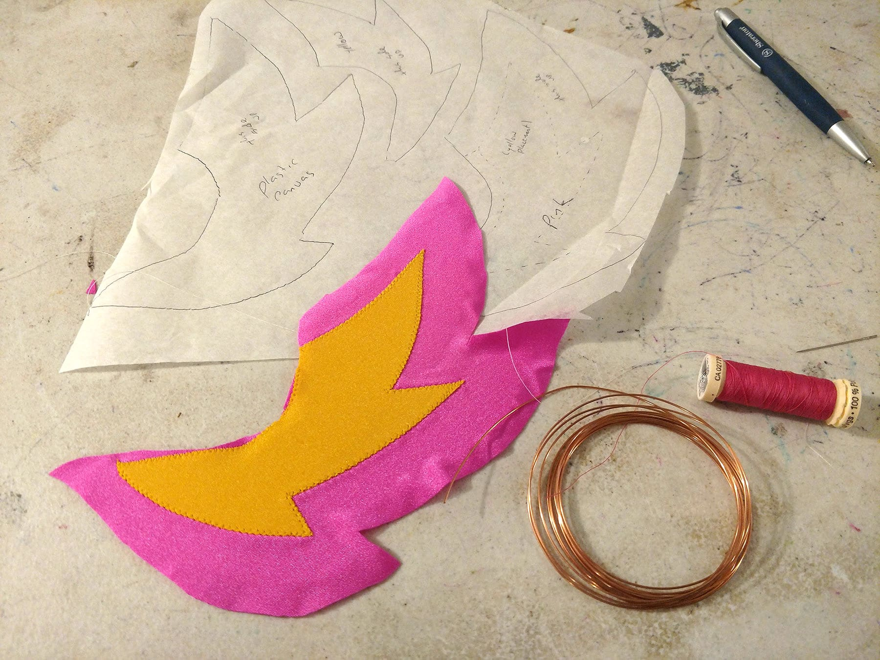 A paper pattern for a headpieces, along with copper coloured cord, pink thread, and a pink and yellow piece of appliqued spandex.