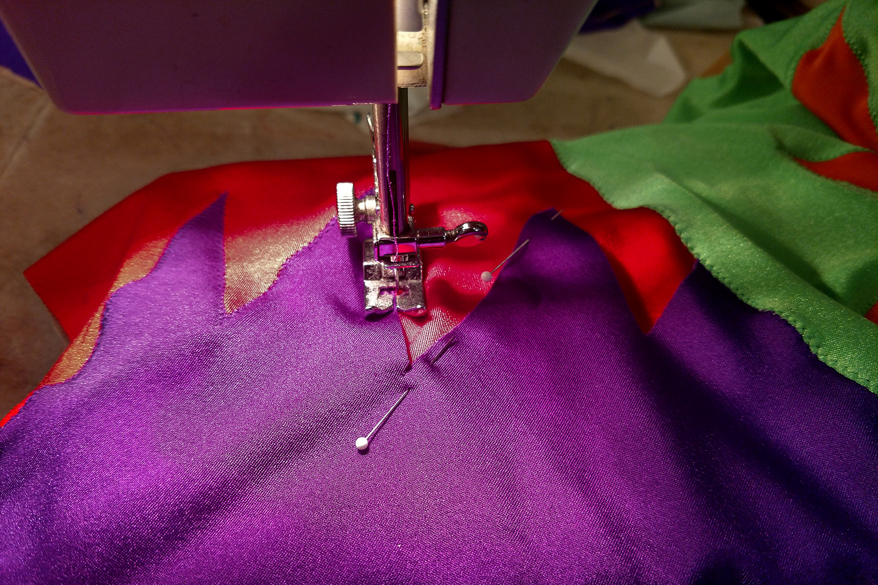 A piece of one of the jazz team synchro suits is being sewn in a machine. Purple is shown being stitched onto red spandex.