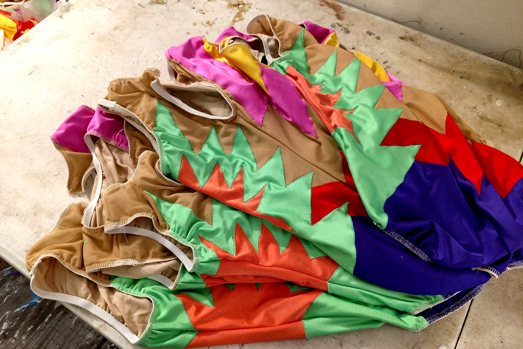 A pile of jazz team synchro suits is shown. They are mostly done, the elastic is yet to be flipped and stitched down.