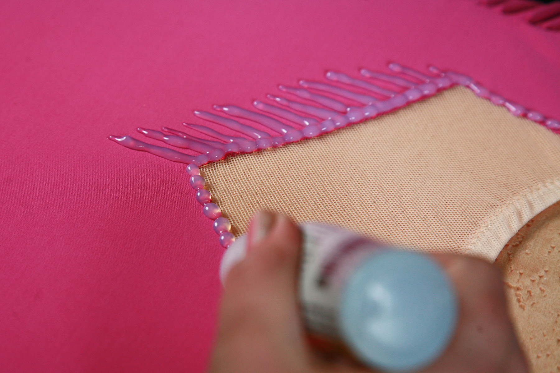 A tube of foil glue is piping a design on a bright pink spandex skating dress.