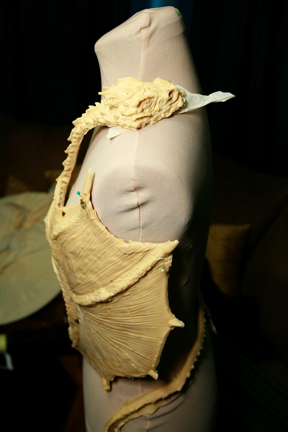 Side view of the freshly unmolded - and beige - latex dragon top, set up on a dress form.
