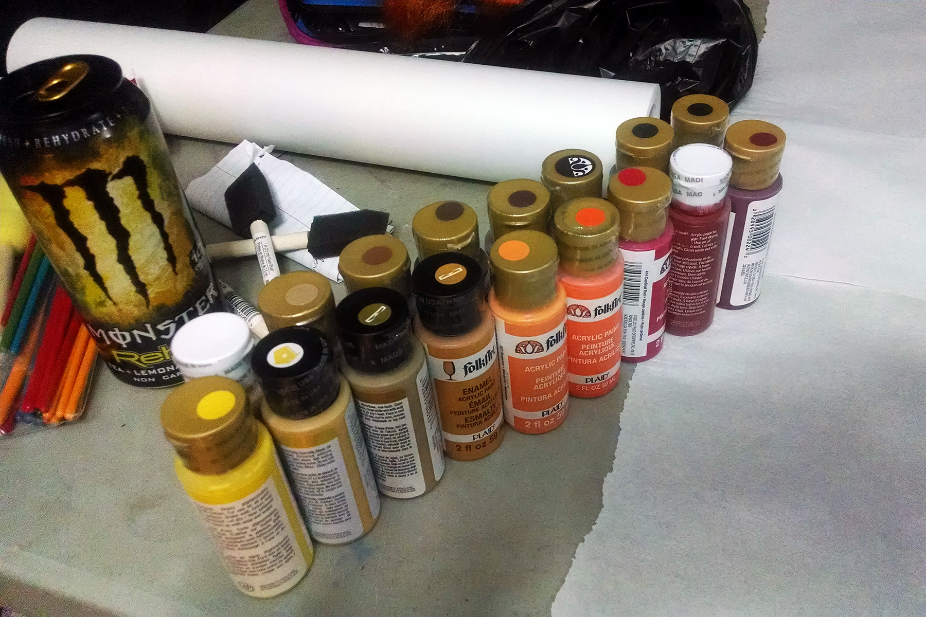 18 different tubes of acrylic paint - yellows, oranges, gold, red, and black - are arranged in two rows on a work table.