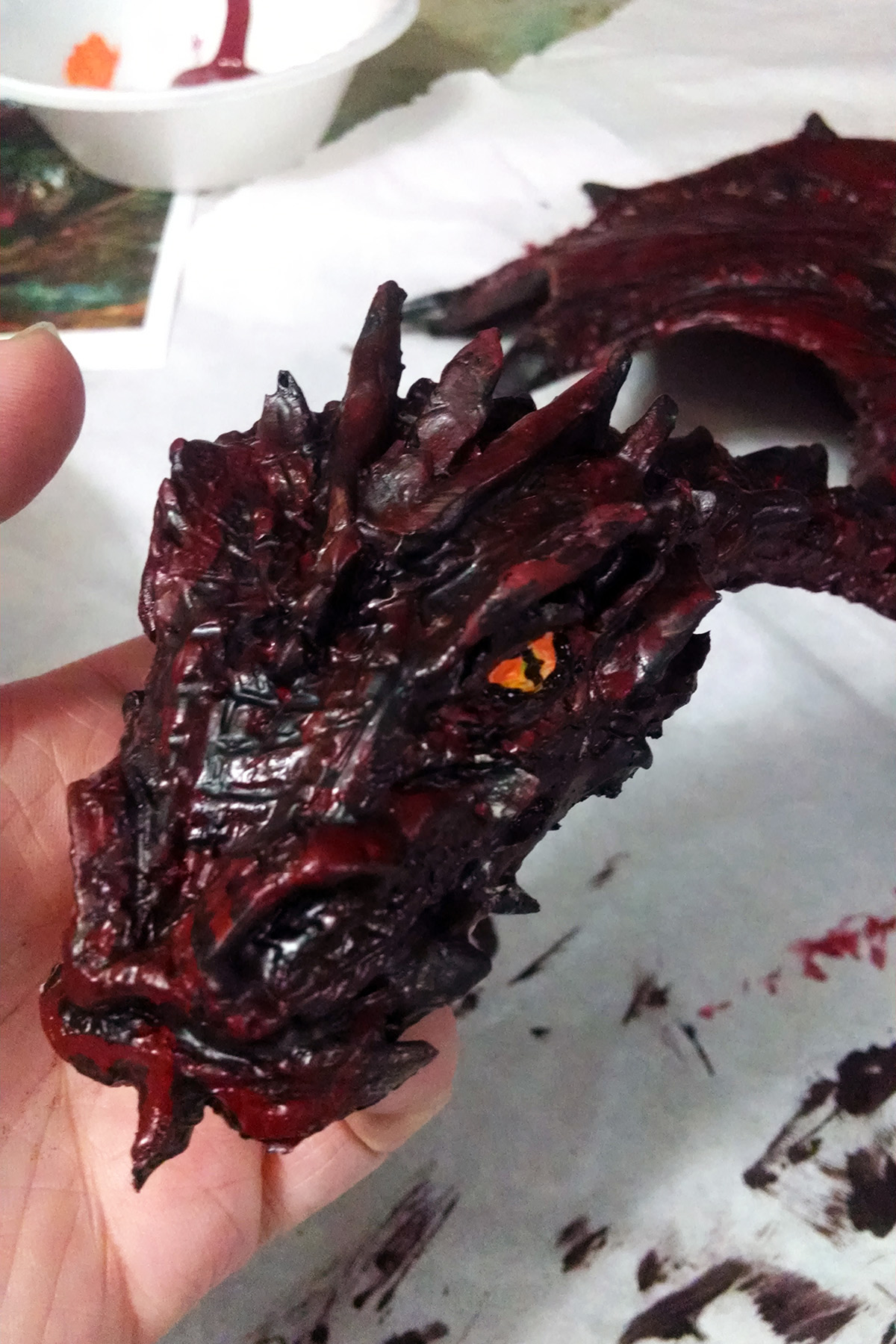 A hand holds up the molded latex Smaug's face, which now has yellow and orange eye detailing added to it.