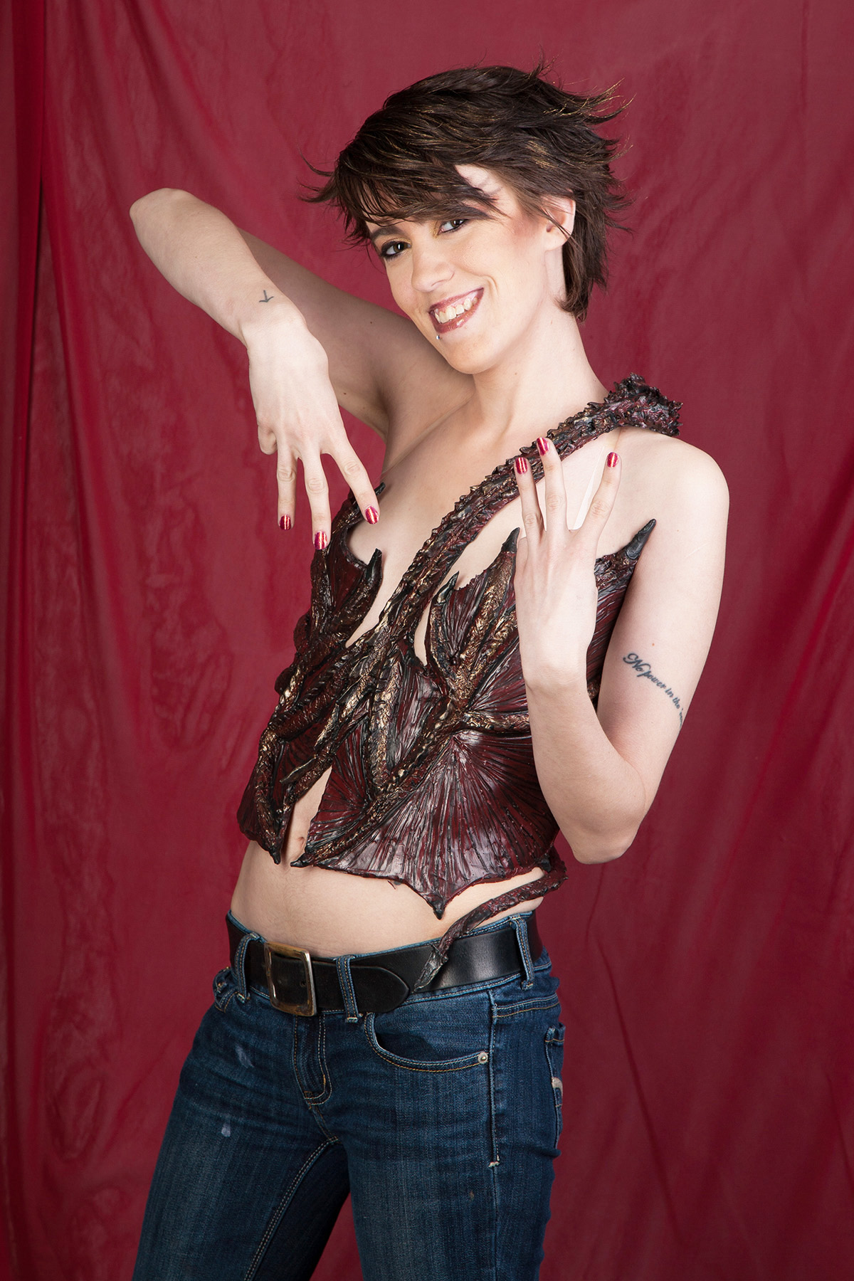 A beautiful young woman with short hair is standing up in front of a red background. She is wearing a dark burgundy latex, 3D sculpted dragon top. It wraps around her torso, and looks like Smaug.