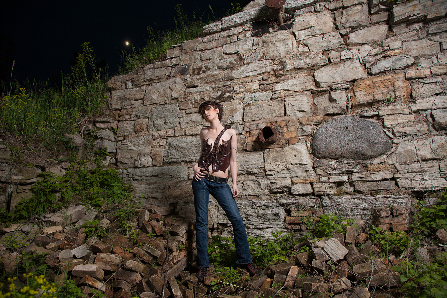 A beautiful young woman with short hair is standing in front of a rock retaining wall, wearing a dark burgundy latex, 3D sculpted dragon top. It wraps around her torso, and looks like Smaug.