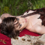 A beautiful young woman with short hair is laying on some rocks, wearing a dark burgundy latex, 3D sculpted dragon top. It wraps around her torso, and looks like Smaug.