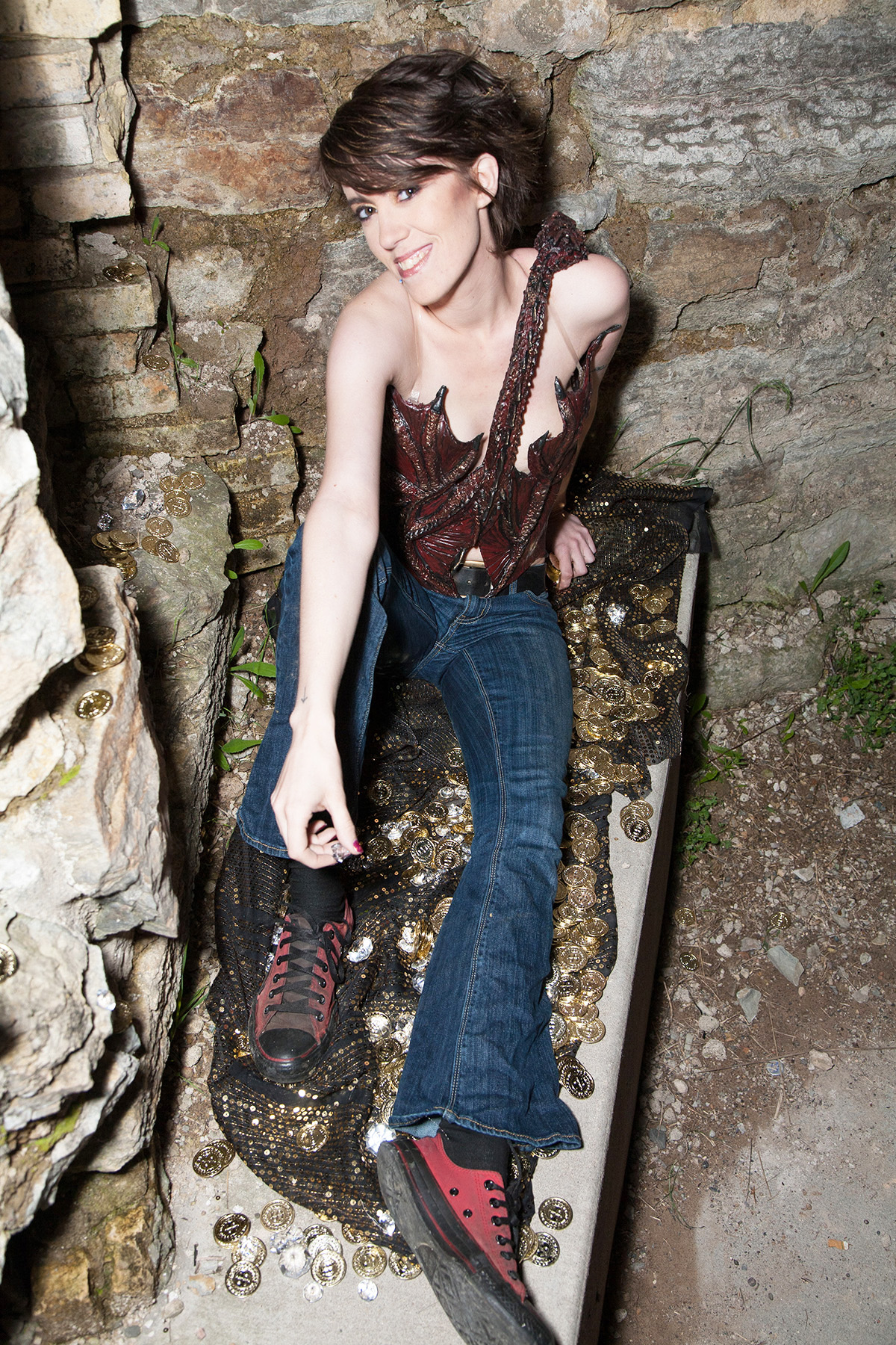 A beautiful young woman with short hair is sitting on a pile of rocks, in front of a rock retaining wall, wearing a dark burgundy latex, 3D sculpted dragon top. It wraps around her torso, and looks like Smaug.