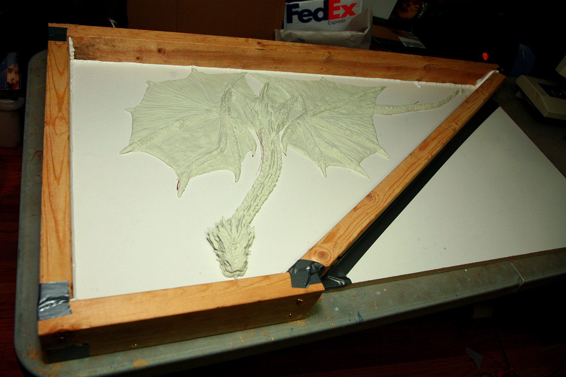 The clay dragon on white board has had a wooden wall built around it.