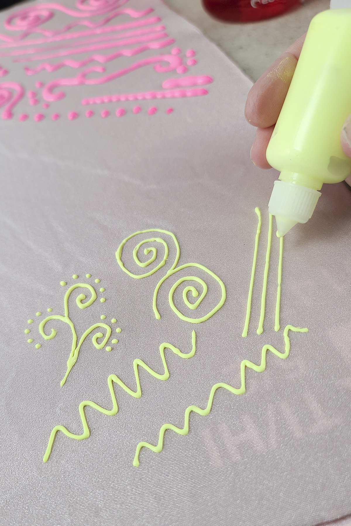 A small fabric paint bottle with neon yellow stretch paint is piping a design onto light pink spandex.