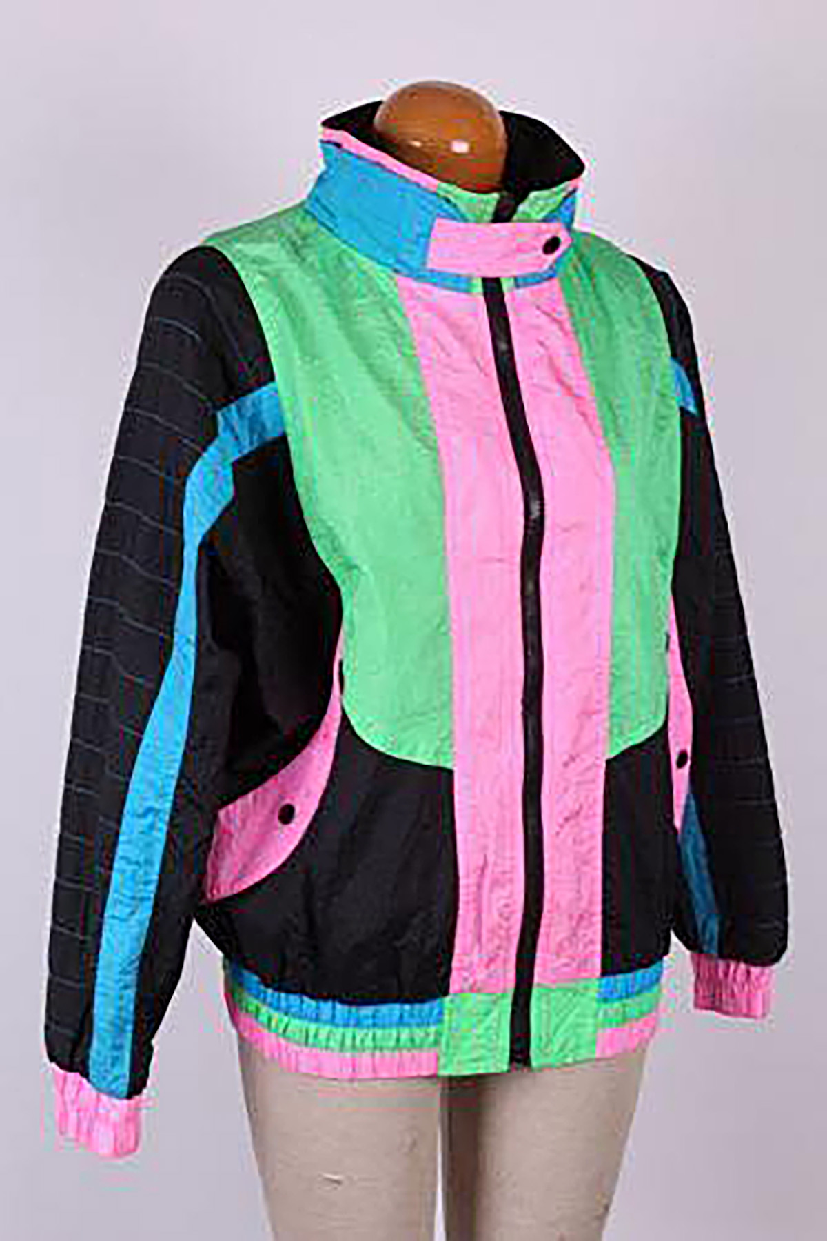 An 80s style tracksuit jacket on a mannequin. It's black, pink, sky blue, and apple green.