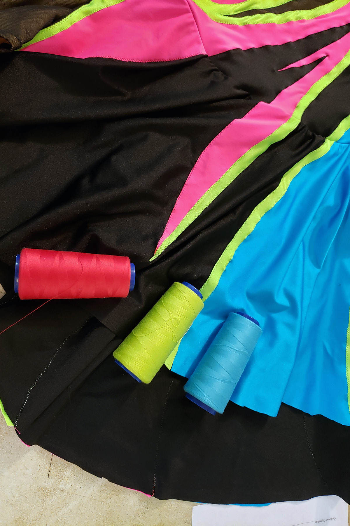 3 large serger cones of thread in pink, lime green, and sky blue are resting on the skirt section of this skating dress.
