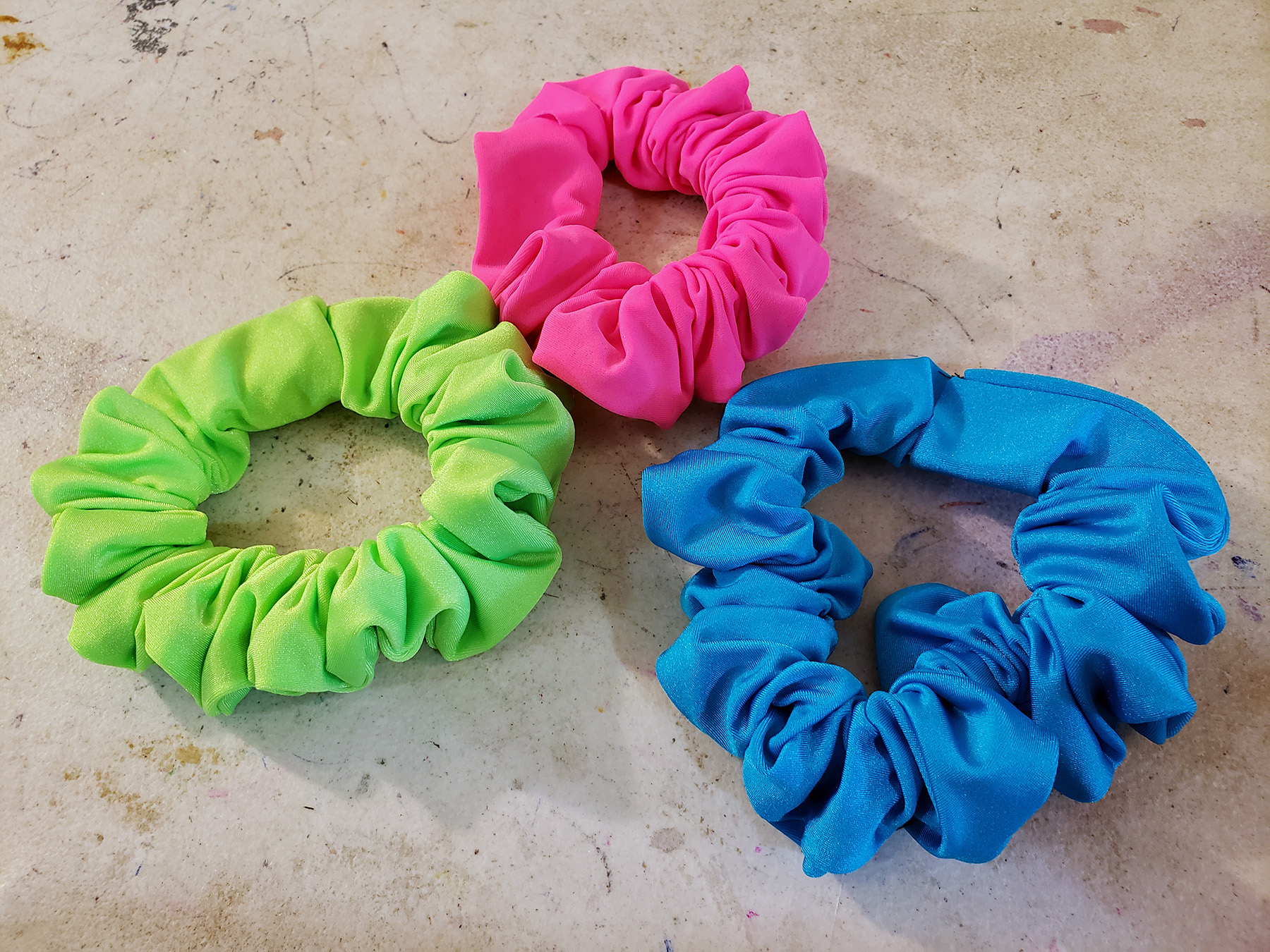 3 scrunchies on a grey work table. Hot pink, lime green, and sky blue.