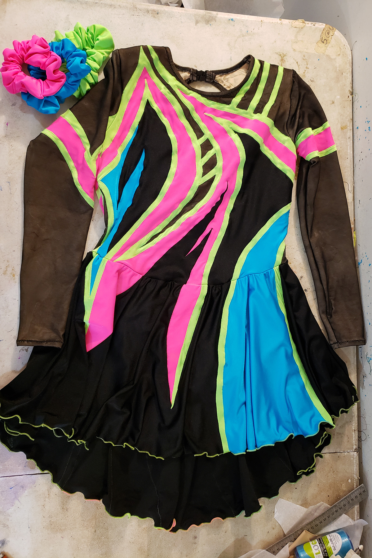 A front view of the 80's themed figure skating dress. It is black spandex and black mesh, with swirls of neon pink, lime green, and sky blue on it. There are 3 matching scrunchies laid out beside it.