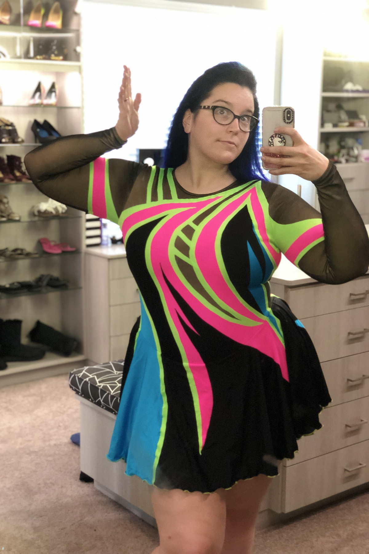 A gorgeous woman with black and blue hair and glasses takes a selfie wearing the 80's themed skating dress.