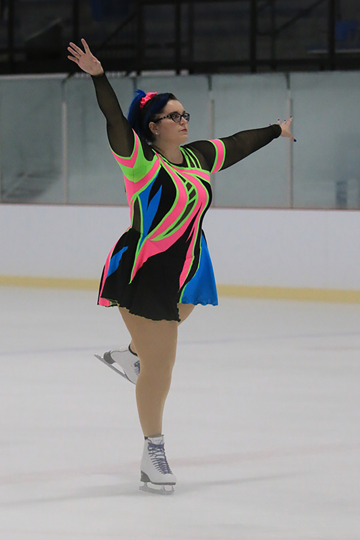 A gorgeous dark haired woman with glasses is alone on the ice, skating her routine in this 80s themed skating dress.