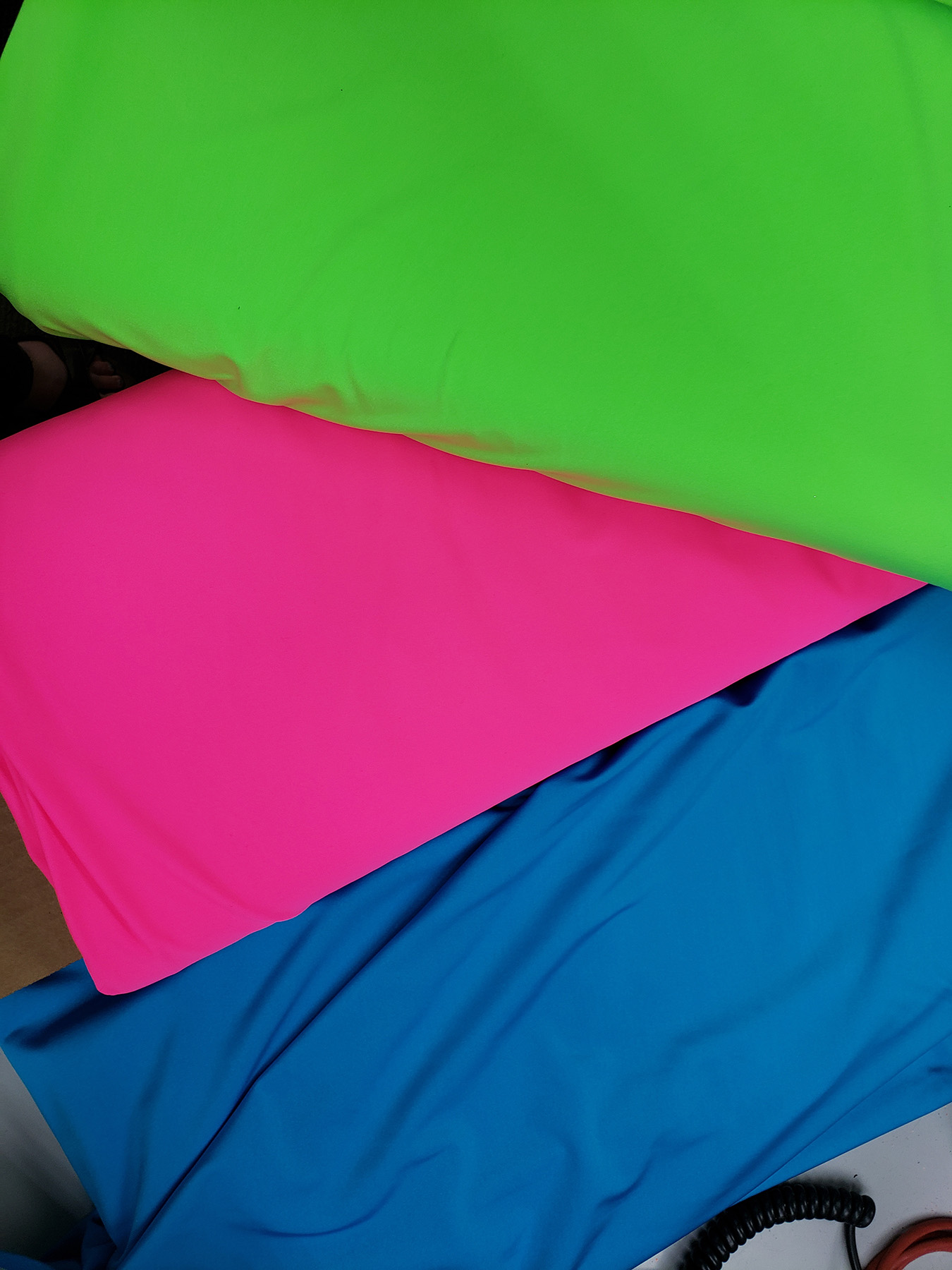 Stacked bolts of fabric in lime green, hot pink, and sky blue.
