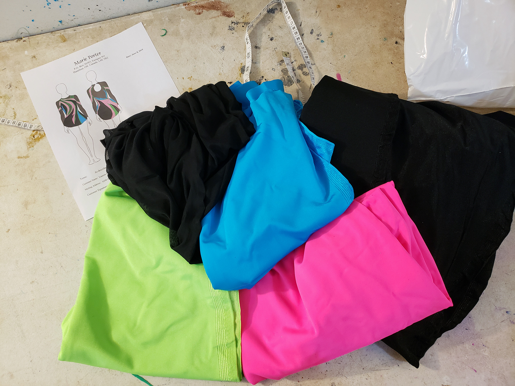 A pile of fabric on a work table - black spandex, black mesg, neon pink, neon green, and sky blue spandex.