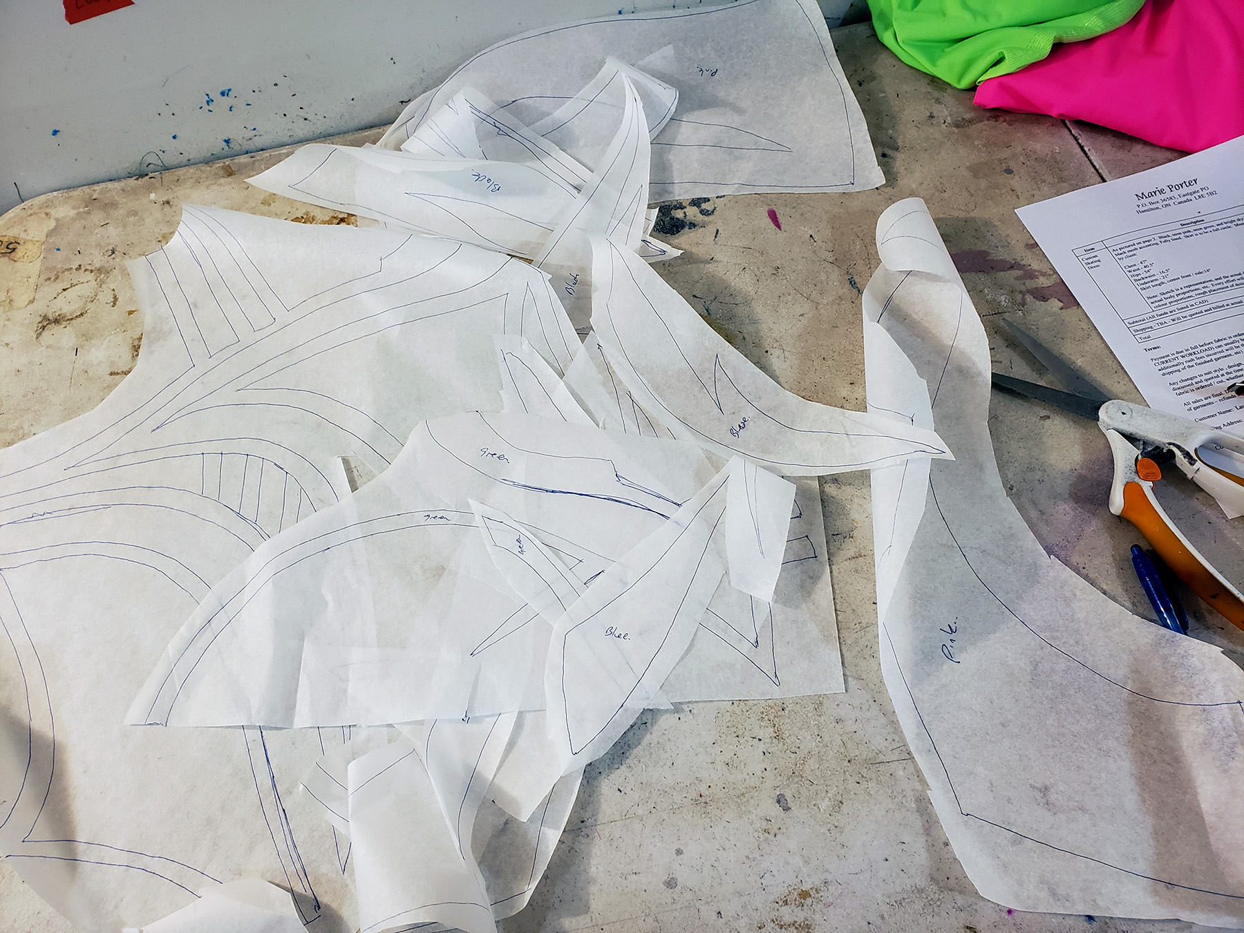 A pile of hand drawn pattern pieces made from exam table paper, on a grey work table.