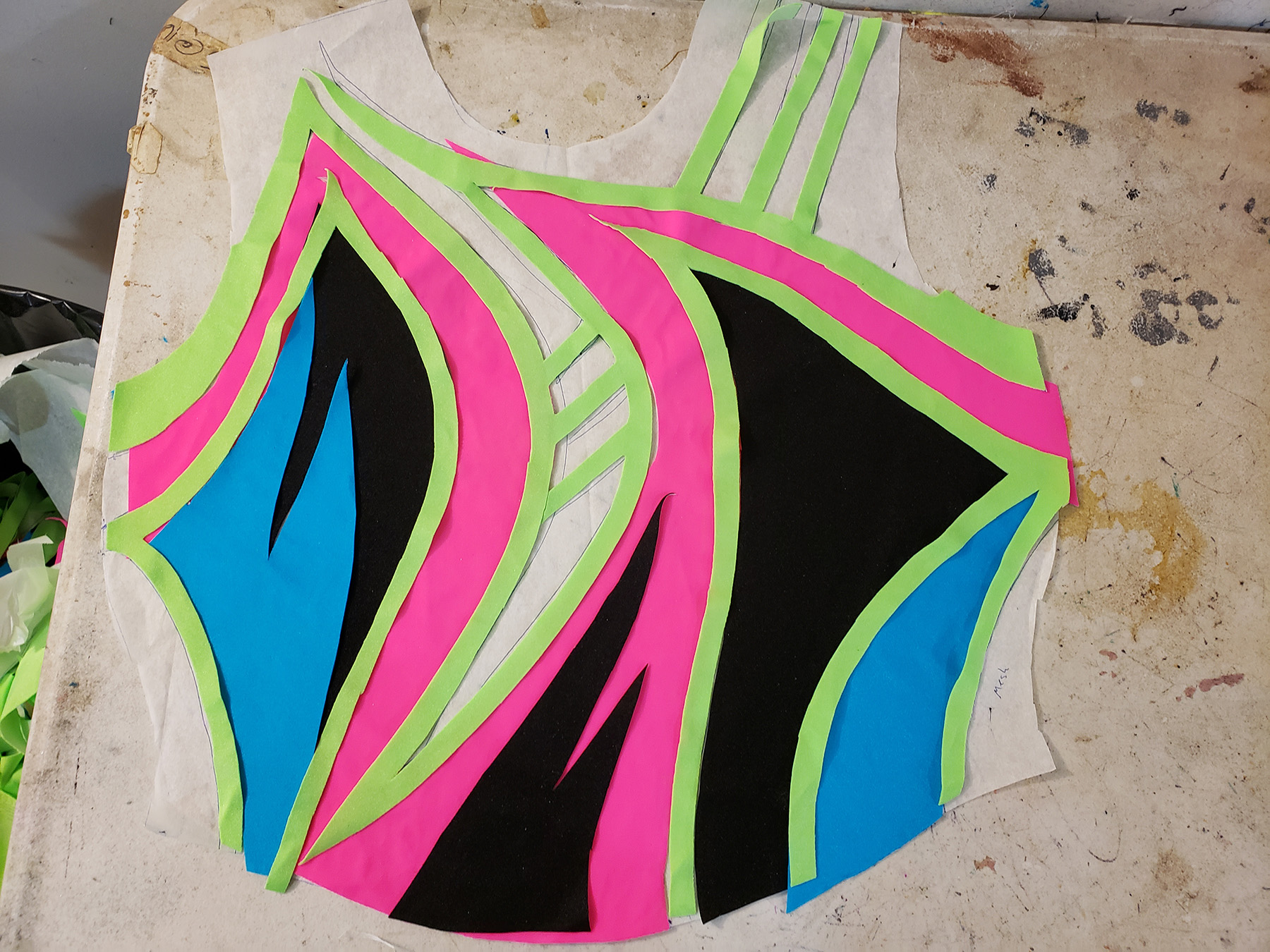 Applique pieces for the front of an 80s style skating dress are laid out on top of the master pattern.
