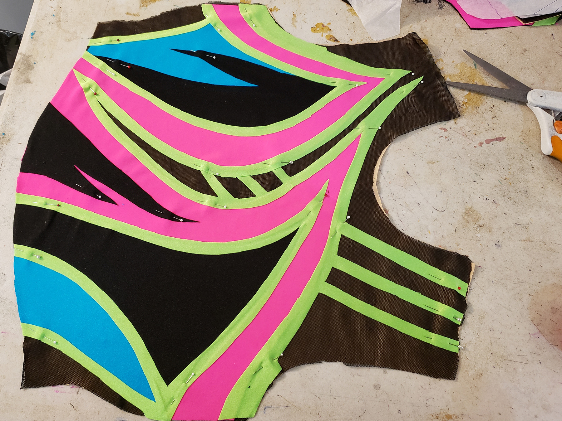 The sewn front bodice of an 80s style figure skating dress. The base is black spandex and mesh, with designs in hot pink, lime green, and sky blue on top.