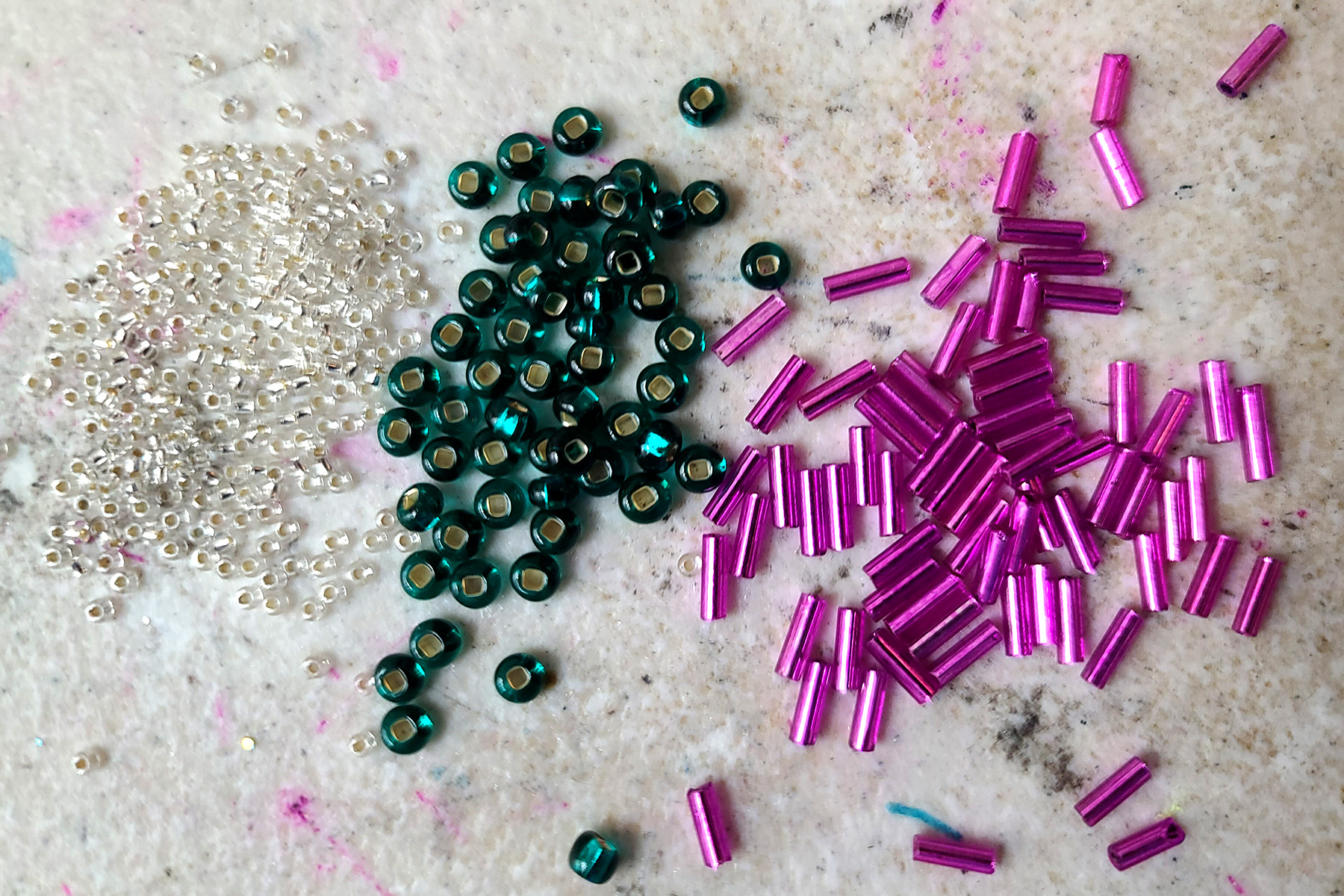 Clear seed beads, green rocaille beads, and dark pink bugle beads, on a grey work surface.