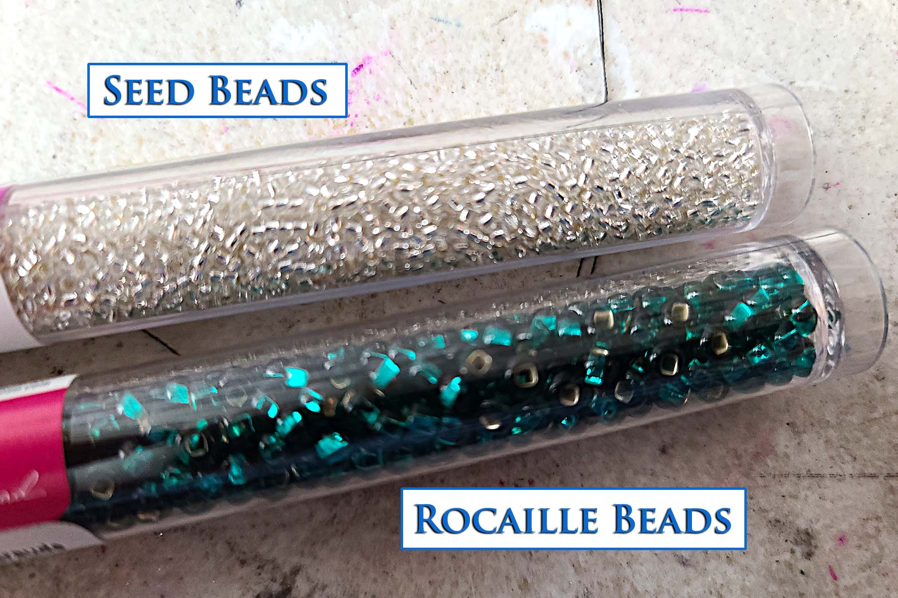 2 long, clear plastic tubes filled with beads. One has clear seed beads, the other has green rocaille beads in it.