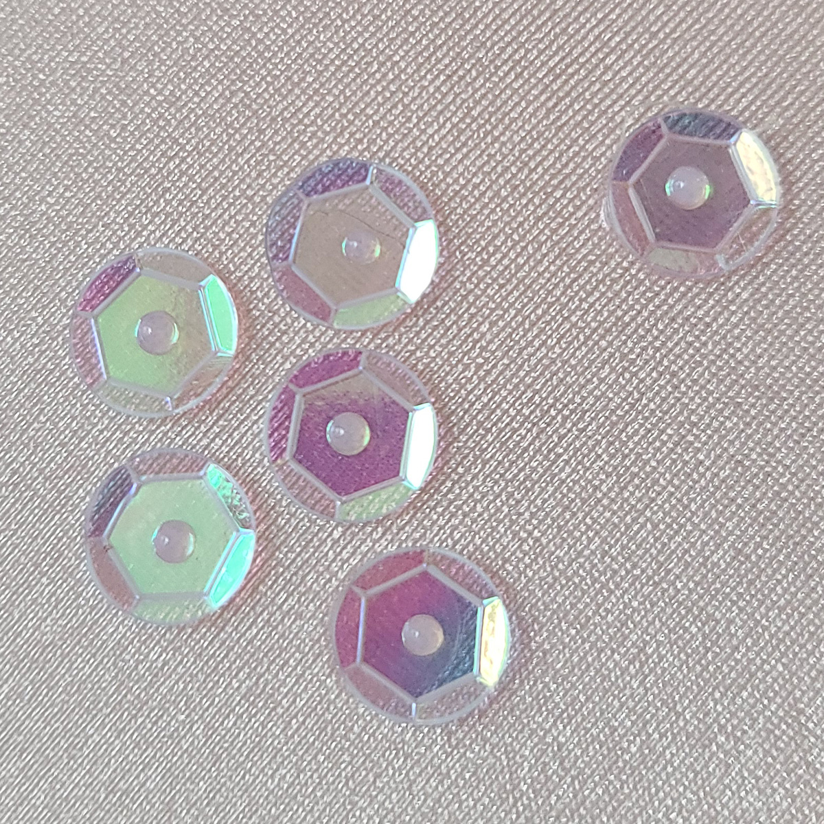 Several clear, iridescent faceted sequins, glued to a light pink stretched spandex.