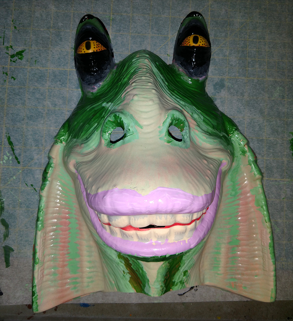 A Jar Jar Binks mask, repainted with a green and black design... and pink lipstick.