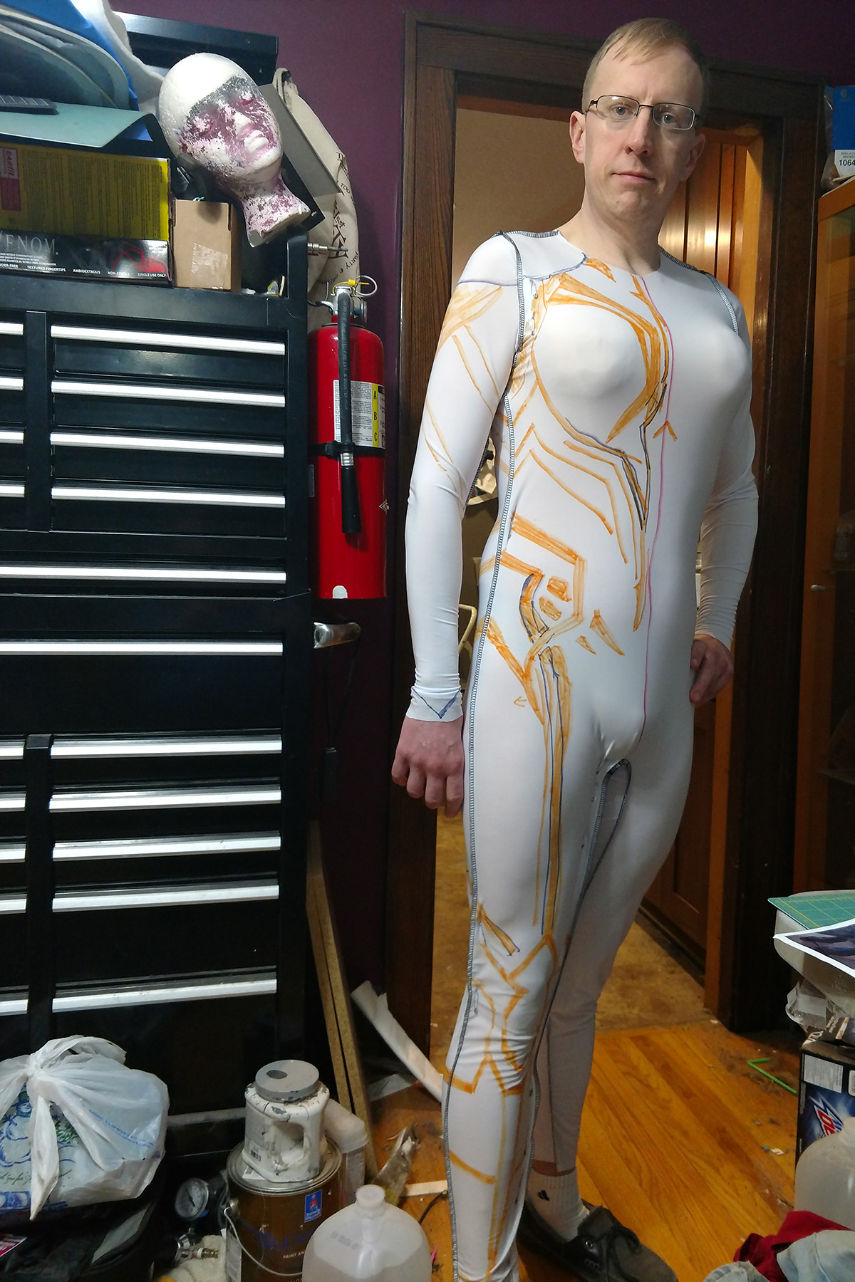 A blonde man with glasses wearing a full body white spandex bodysuit, with orange designs drawn on it.