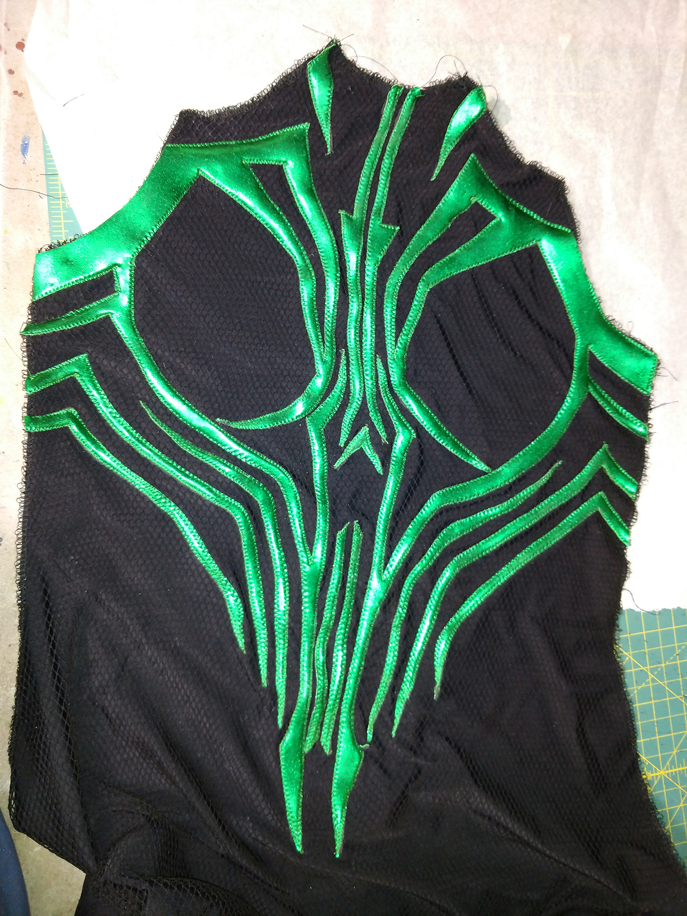 An intricate design of shiny green spandex, stitched down in place on a piece of textured black spandex.