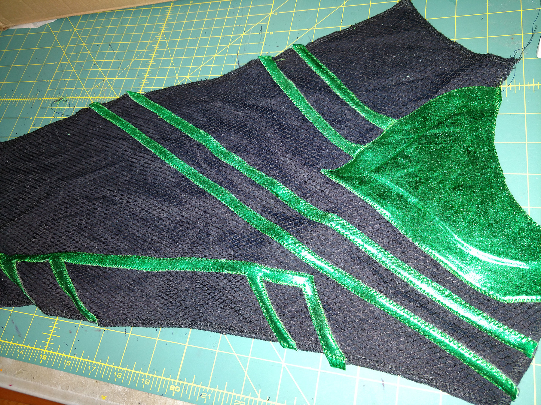 Lines of shiny green spandex, stitched down to a sleeve cut from textured black spandex.