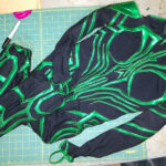 A sewn together Hela costume, laid out on a green work surface.