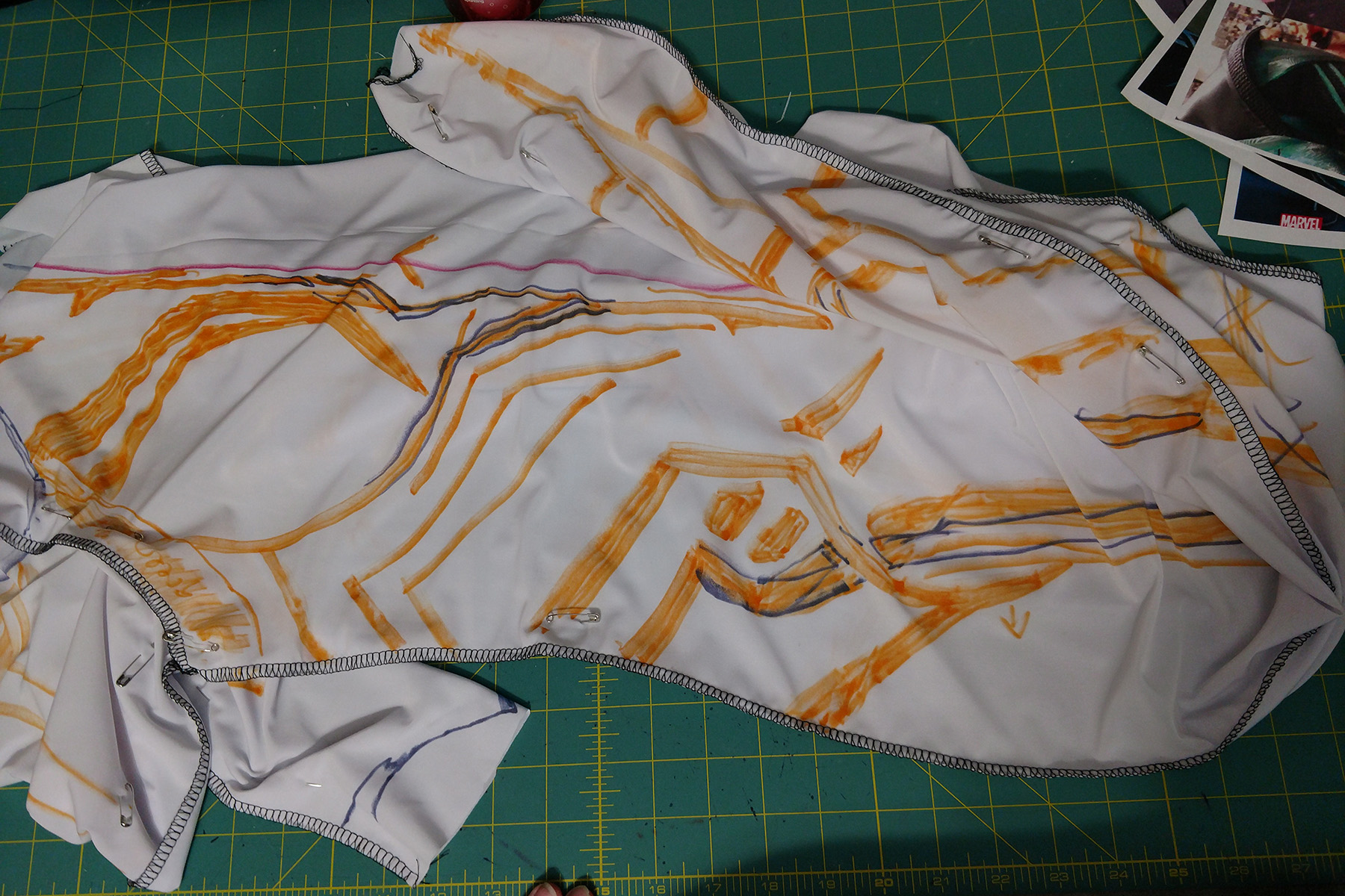 A white bodysuit with orange markings on it, laid out on a green work surface.