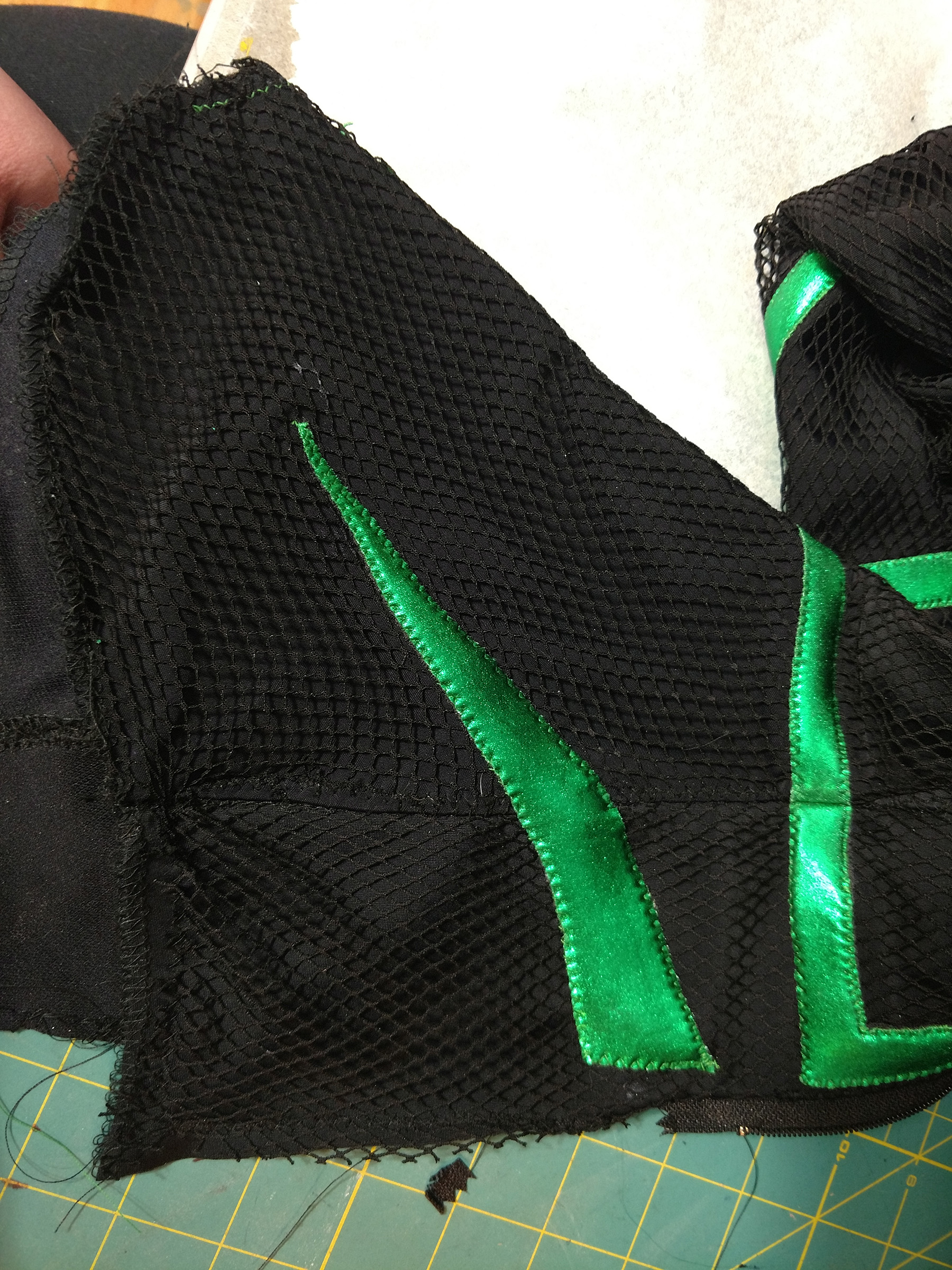 """A close up view of a black spandex """"foot"""" part of the costume, with two pieces of shiny green spandex stitched across it."""