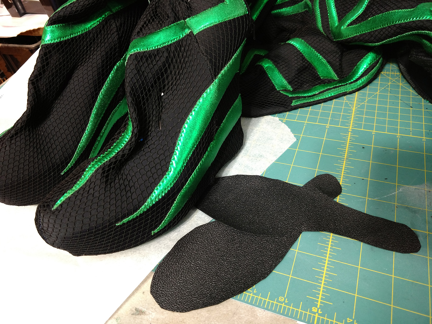 A close up view of the feet of the Hela cosplay, next to two black soles.