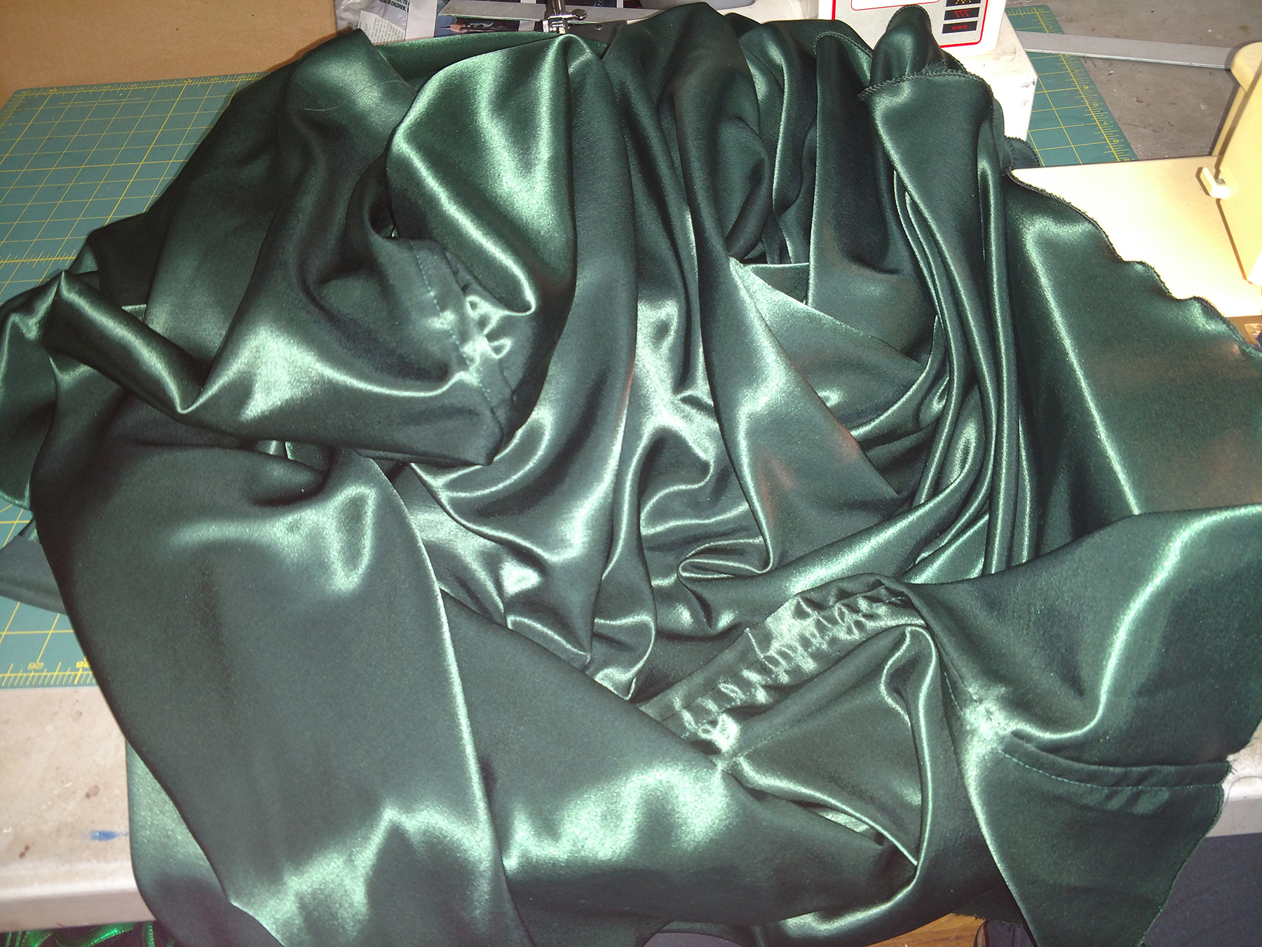 A large green satin cape is bunched up at a sewing machine.