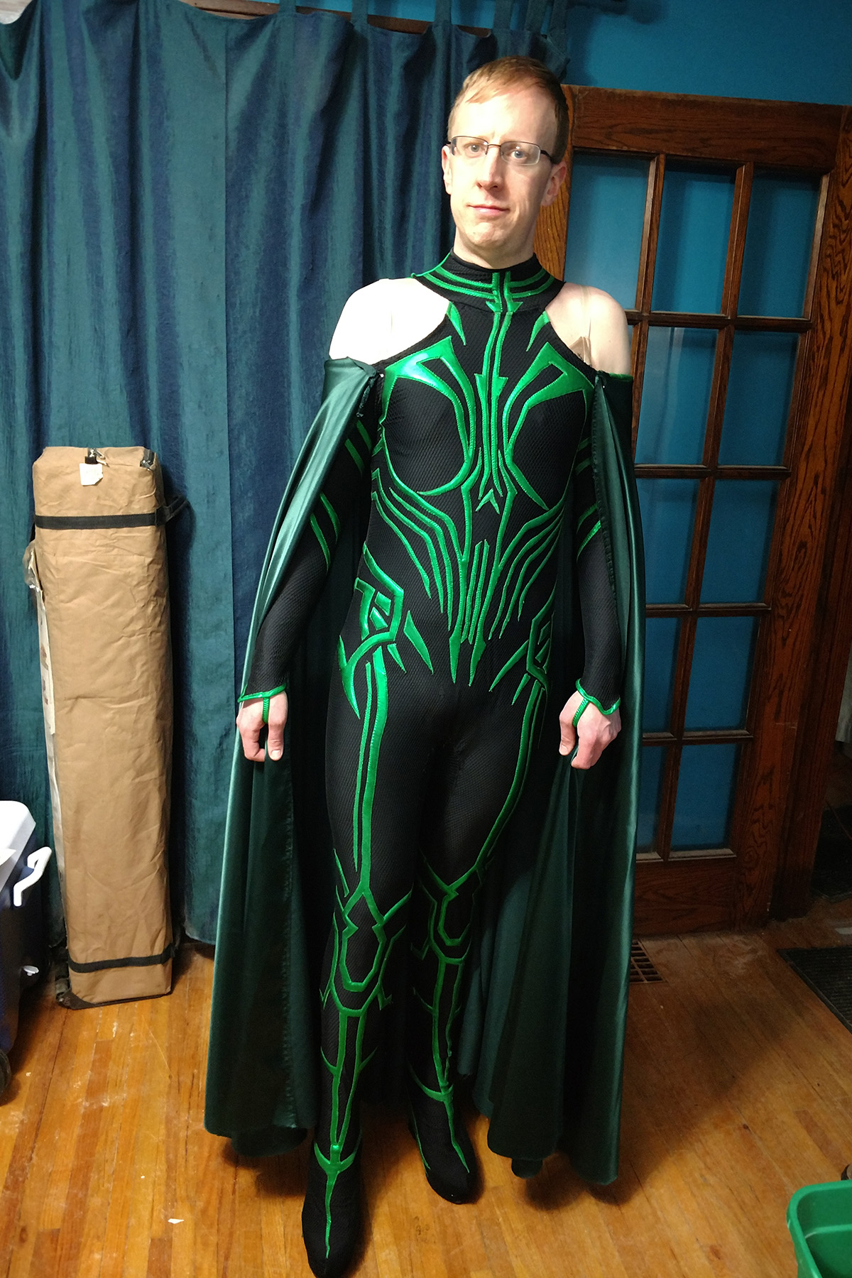 A front view of a blonde man wearing an MCU Hela costume.  This time, there is a long, full green cape attached.