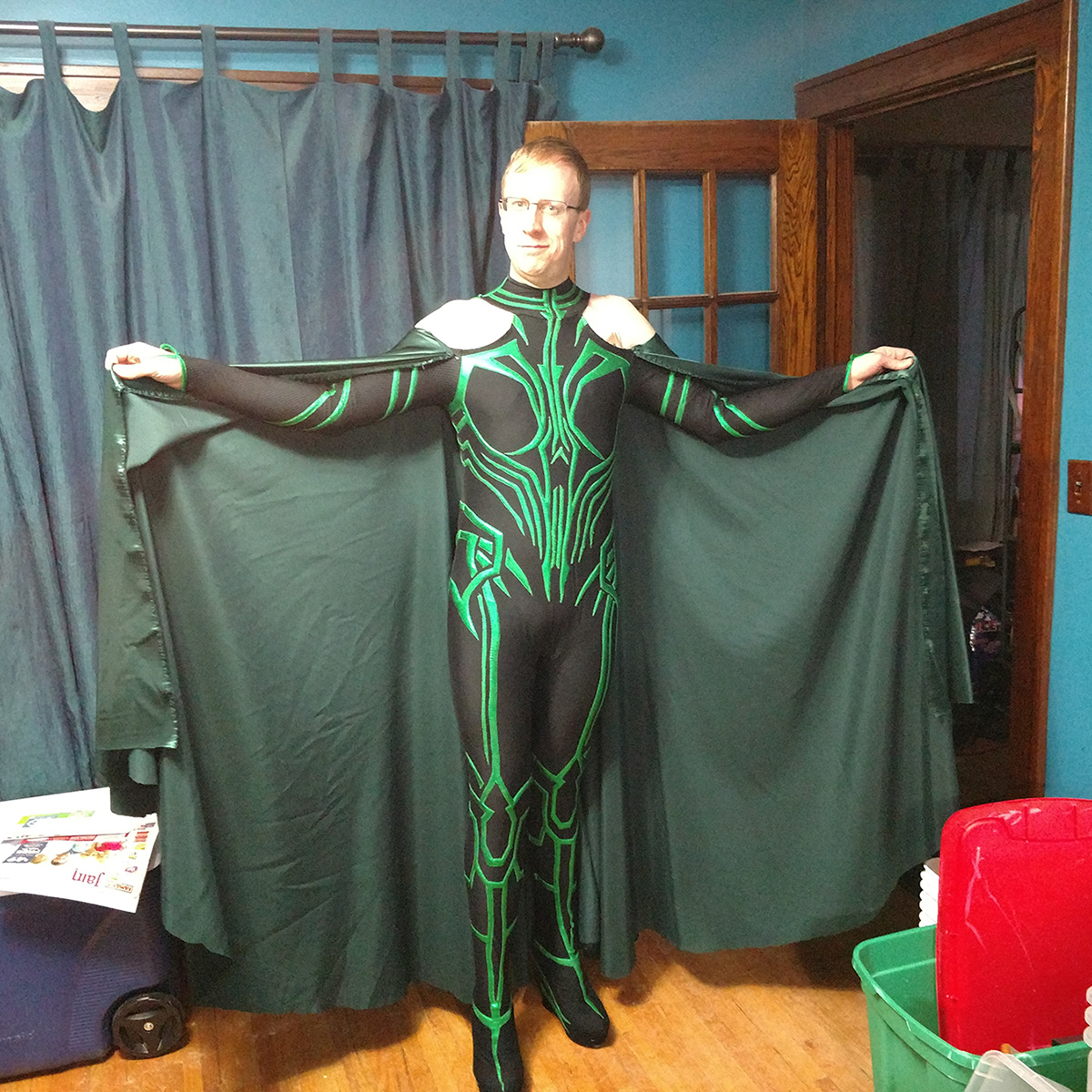 A front view of a blonde man in glasses, wearing an MCU Hela cosplay.  His arms are extended out to the side, holding up the cape ends to show the fullness.