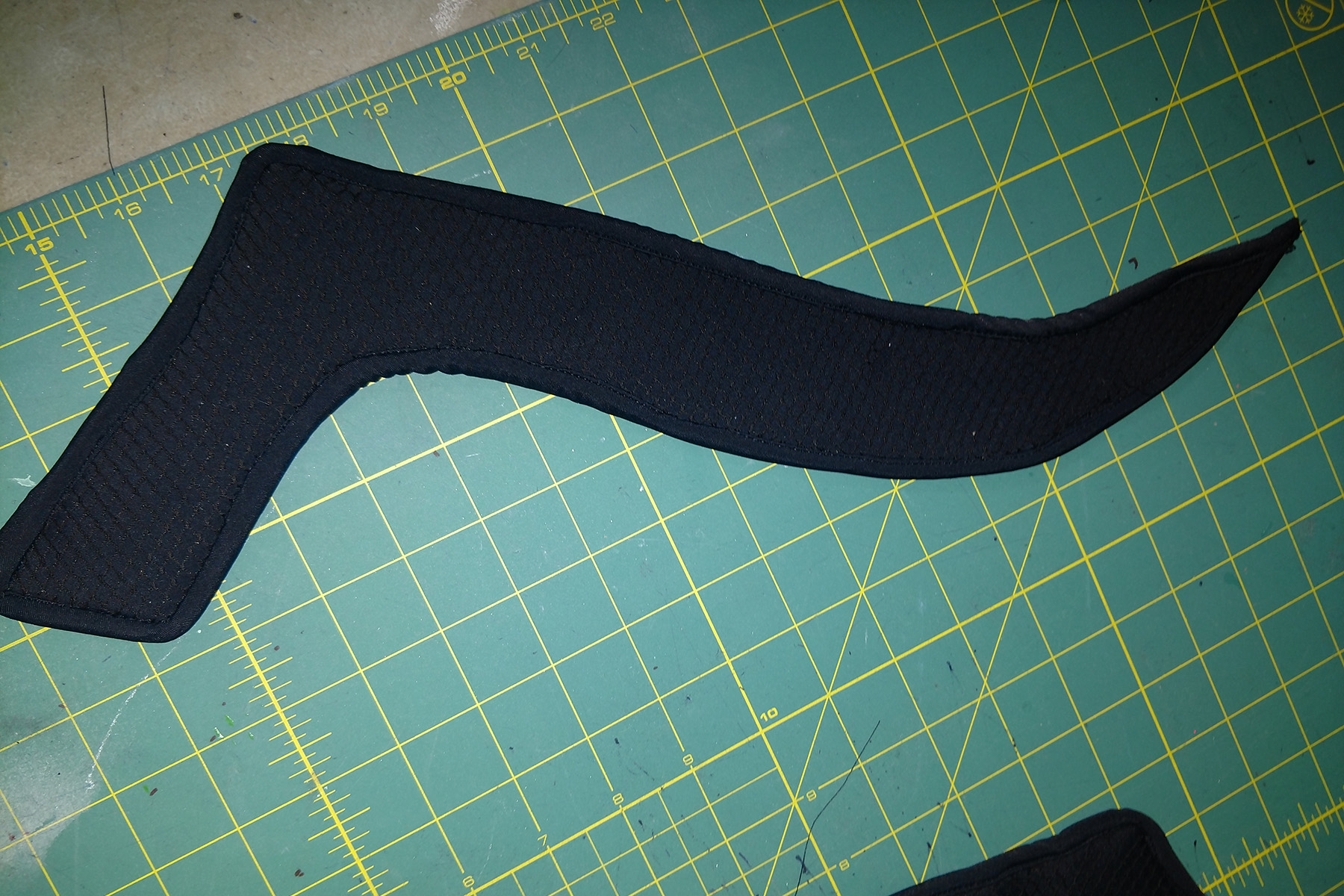 """A vaguely """"L"""" shaped cruved piece of textured black spandex, laid out on a green work surface."""