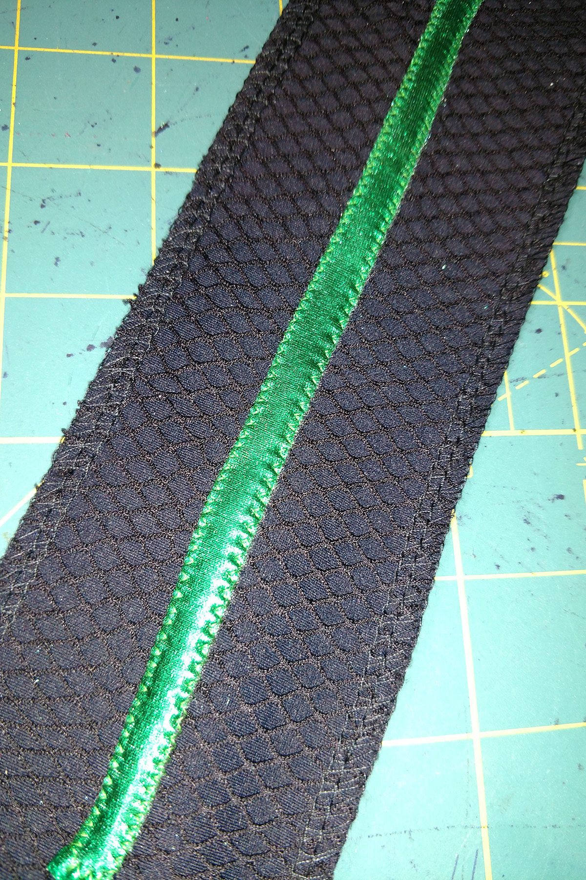 A strip of textured black fabric with a line of metallic green spandex stitched down on it.