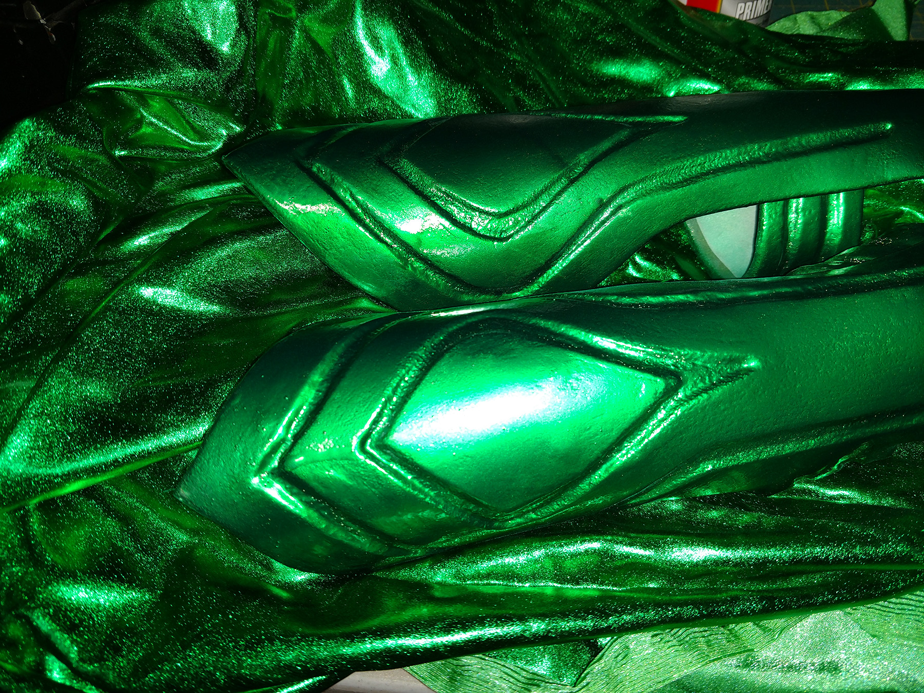 A pair of metallic green Hela bracers are shown against a pile of matching metallic green spandex.