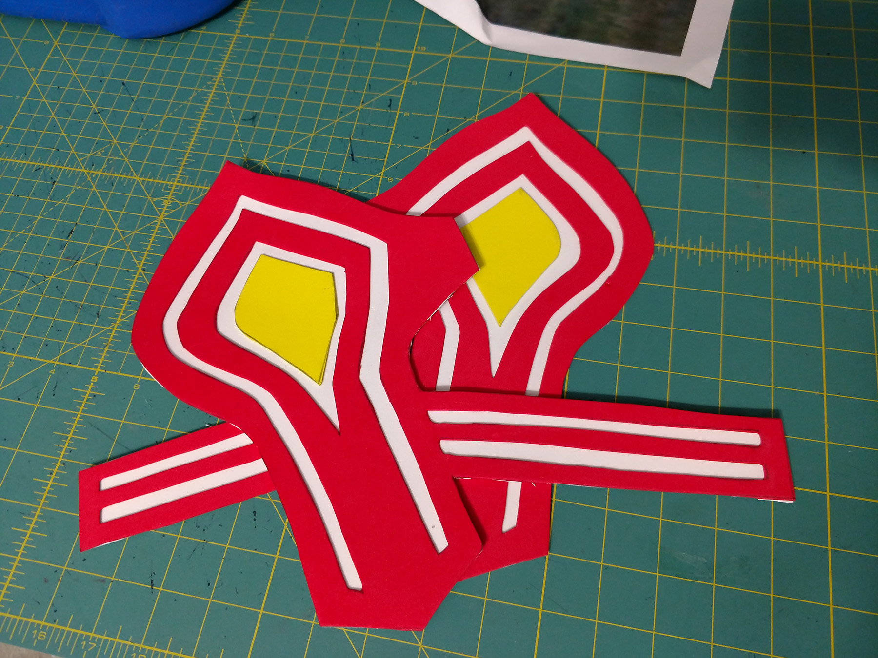 Two bas e bracers made from craft foam. Red and yellow design pieces have been glued down onto a white base piece.