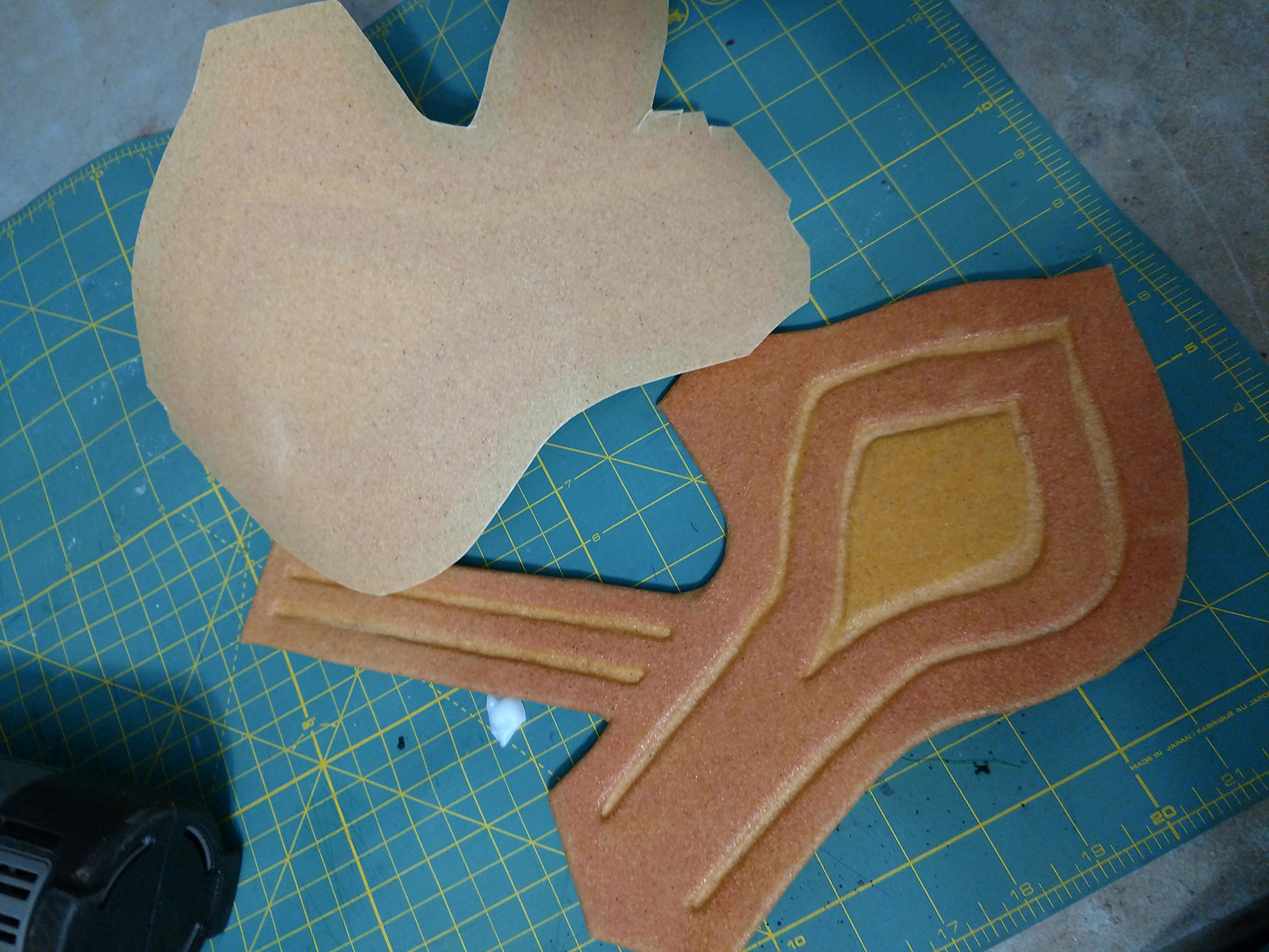 One bracer with the worbla molded down into the design is shown next to a loose piece of worbla cut to shape, ready for the second bracer.