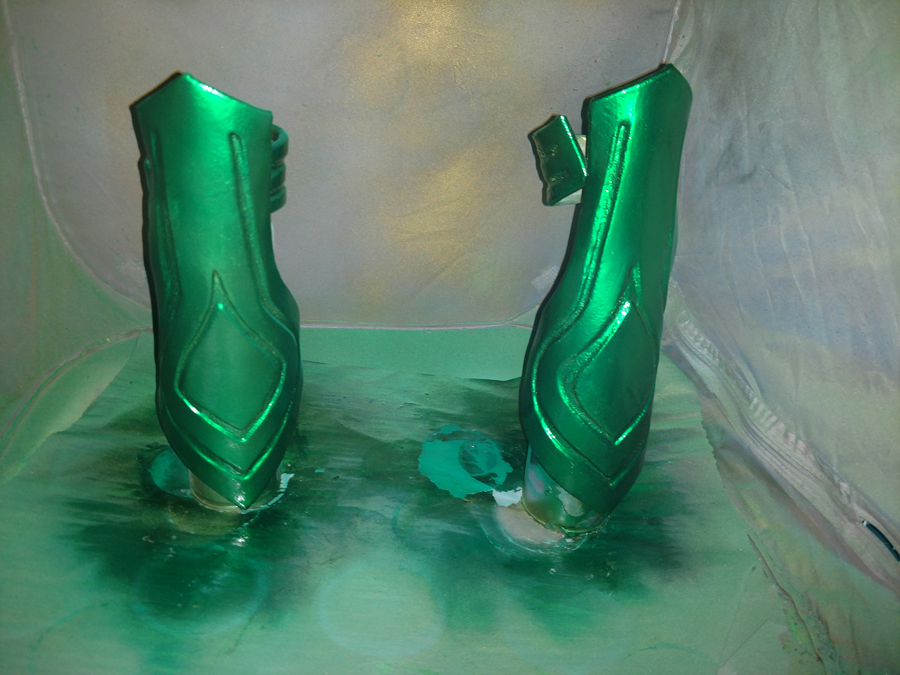 Shiny metallic green Hela bracers are shown against a grey backdrop that is covered in green and gold spray paint.