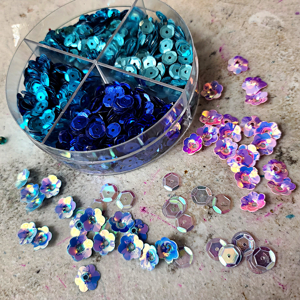 A clear tin of blue sequins is shown sitting behind piles of light pink and blue sequins.