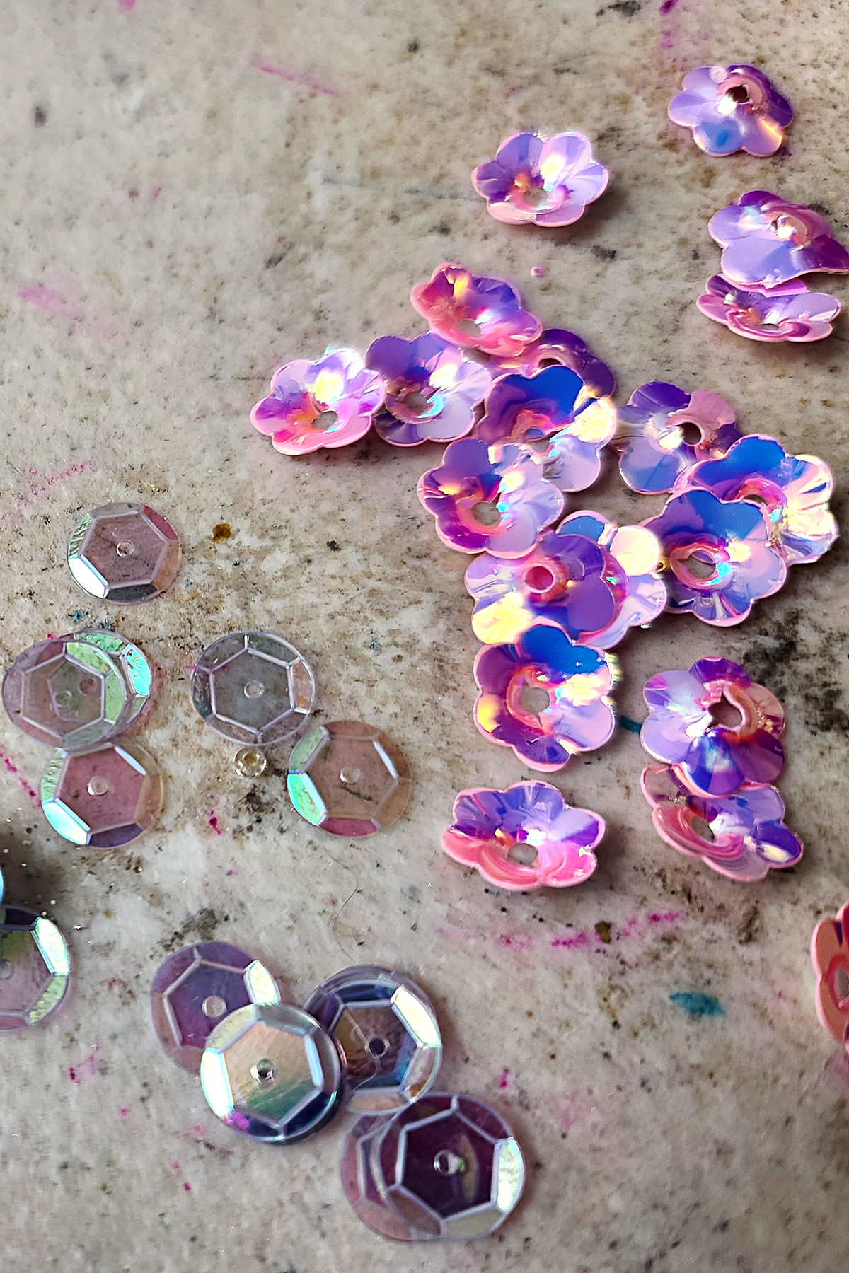 CLear iridescent sequins and pink flower shaped sequins.