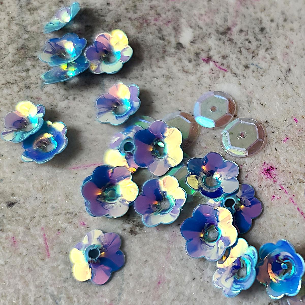 A pile of light blue iridescent flower shaped sequins.