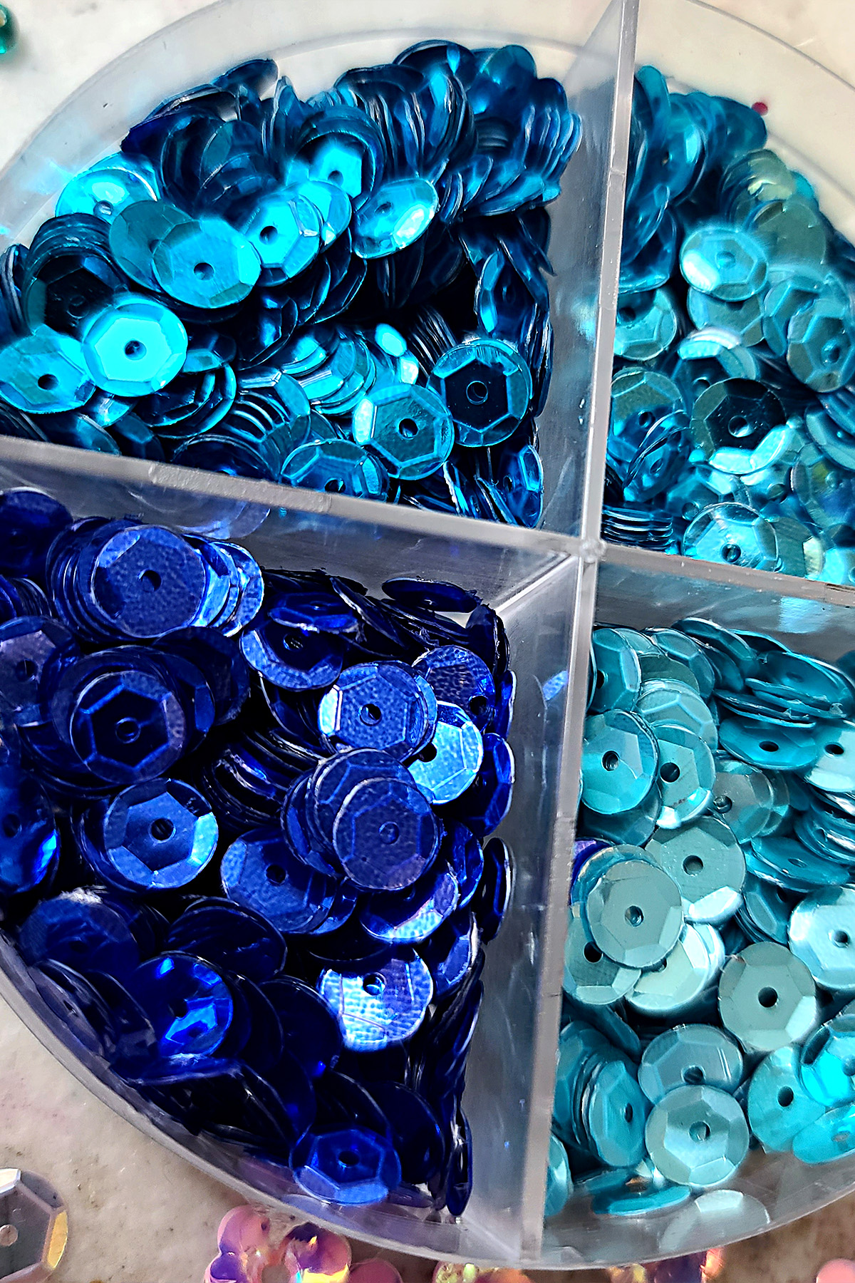 A close up photo of a tin of blue sequins in various shades.